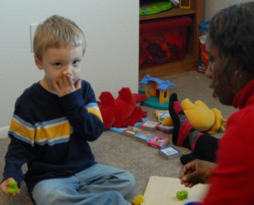 A child playing with someone that seems like a therapist