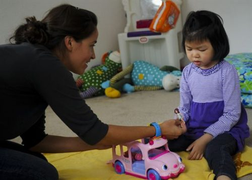 A child playing with her toy. Her mother is playing with her